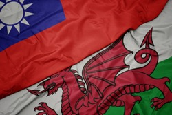 waving colorful flag of wales and national flag of taiwan. macro