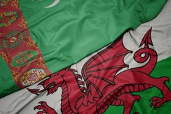 waving colorful flag of wales and national flag of turkmenistan. macro