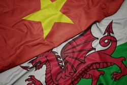 waving colorful flag of wales and national flag of vietnam. macro