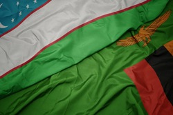 waving colorful flag of zambia and national flag of uzbekistan. macro