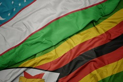 waving colorful flag of zimbabwe and national flag of uzbekistan. macro