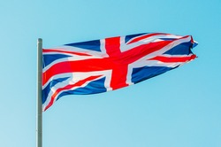 Waving colorful Great Britain flag on blue sky