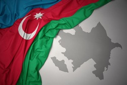 waving colorful national flag of azerbaijan on a gray map background.