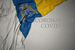waving colorful national flag of canary islands on a gray background with text coronavirus covid-19 . concept.