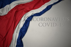 waving colorful national flag of costa rica on a gray background with text coronavirus covid-19 . concept.
