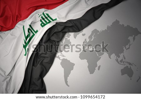 waving colorful national flag of iraq on a gray world map background.