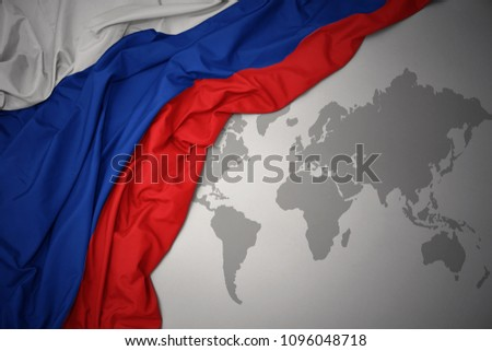 waving colorful national flag of russia on a gray world map background. #1096048718