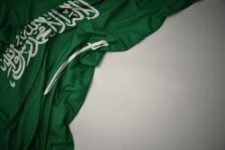 waving colorful national flag of saudi arabia on a gray background.