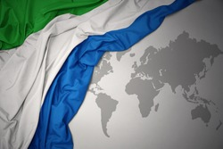 waving colorful national flag of sierra leone on a gray world map background.