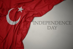 waving colorful national flag of turkey on a gray background with text independence day. concept