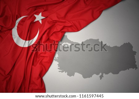 waving colorful national flag of turkey on a gray map background.3D illustration