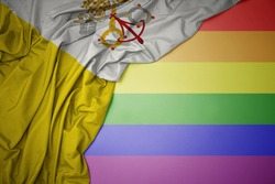 waving colorful national flag of vatican city on a gay rainbow flag background.