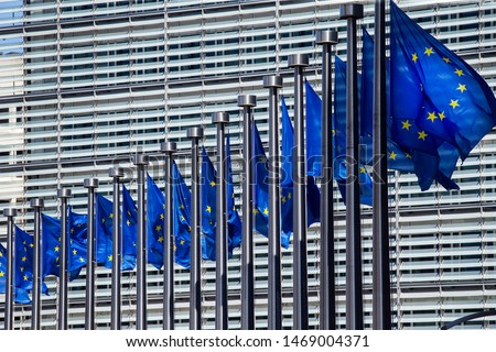 Waving European Union flags outside the European Commission Headquarters, also know as the Berlaymont building, in Brussels, Belgium.