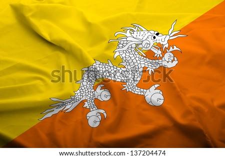 Waving flag of Bhutan. Flag has real fabric texture.