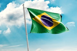 Waving Flag of Brazil in Blue Sky. Brazil Flag on pole for Independence day. The symbol of the state on wavy cotton fabric.