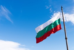 Waving flag of Bulgaria against blue sky with copy space on left