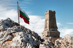 Waving flag of Bulgaria and Shipka memorial monument of Bulgarian liberty