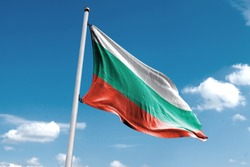 Waving Flag of Bulgaria in Blue Sky. Bulgaria Flag on pole for Independence day. The symbol of the state on wavy cotton fabric.