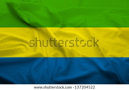 Waving flag of Gabon. Flag has real fabric texture.