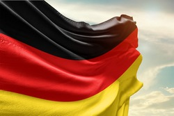 Waving Flag of Germany in Blue Sky. Germany Flag on pole for Independence day. The symbol of the state on wavy cotton fabric.