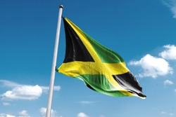 Waving Flag of Jamaica in Blue Sky. Jamaica Flag on pole for Independence day. The symbol of the state on wavy cotton fabric.