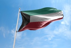 Waving Flag of Kuwait in Blue Sky. Kuwait Flag on pole for Independence day. The symbol of the state on wavy cotton fabric.