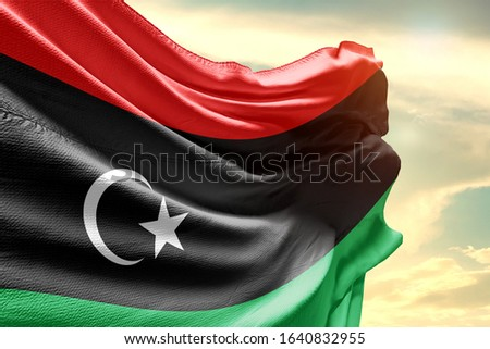 Waving Flag of Libya in Blue Sky. Libya Flag on pole for Independence day. The symbol of the state on wavy cotton fabric. Stockfoto ©