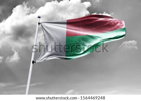 Waving Flag of Madagascar in Sky. Madagascar Flag on pole for Independence day. The symbol of the state on wavy cotton fabric.