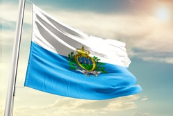 Waving Flag of San Marino in Blue Sky. San Marino Flag on pole for Independence day. The symbol of the state on wavy cotton fabric.