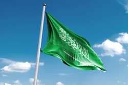 Waving Flag of Saudi Arabiain Blue Sky. Saudi ArabiaFlag on pole for Independence day. The symbol of the state on wavy cotton fabric.