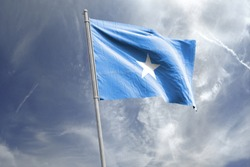 Waving Flag of Somalia in Blue Sky. Somalia Flag on pole for Independence day. The symbol of the state on wavy cotton fabric.