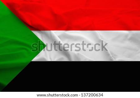 Waving flag of Sudan. Flag has real fabric texture.