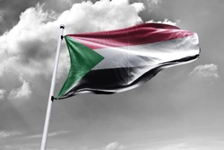 Waving Flag of Sudan in Blue Sky. Sudan Flag on pole for Independence day. The symbol of the state on wavy cotton fabric.