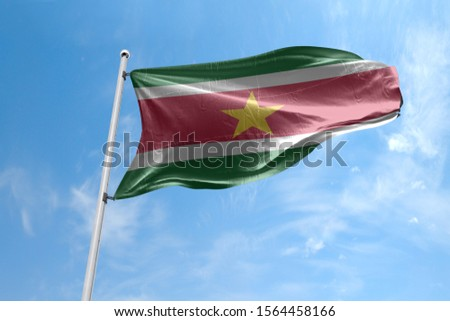Waving Flag of Suriname in Blue Sky. Suriname Flag on pole for Independence day. The symbol of the state on wavy cotton fabric. #1564458166