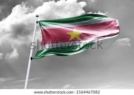 Waving Flag of Suriname in Blue Sky. Suriname Flag on pole for Independence day. The symbol of the state on wavy cotton fabric. #1564467082