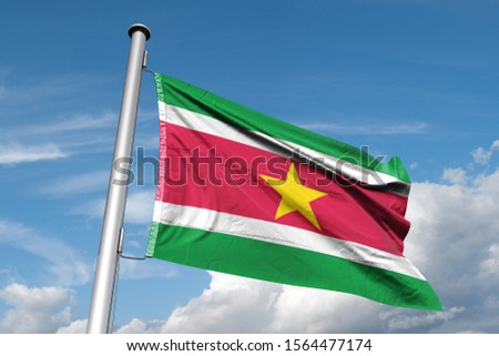 Waving Flag of Suriname in Blue Sky. Suriname Flag on pole for Independence day. The symbol of the state on wavy cotton fabric. #1564477174
