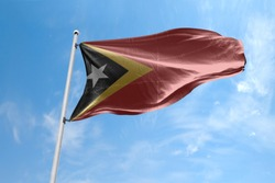 Waving Flag of Timor Leste in Blue Sky. Timor Leste Flag on pole for Independence day. The symbol of the state on wavy cotton fabric.