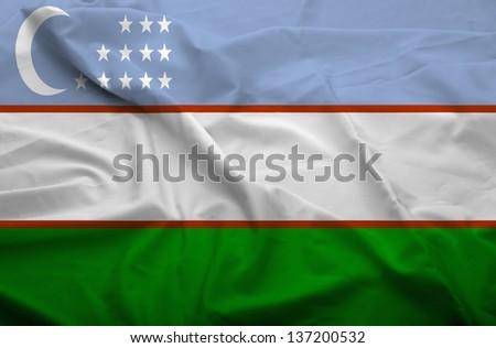 Waving flag of Uzbekistan. Flag has real fabric texture.