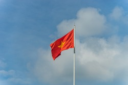 Waving Flag of Vietnam with beautiful sky and clouds. Red flag with yellow star, blue sky with clouds in background. National flag of Vietnam. Popular country for tourism.