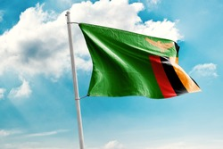 Waving Flag of Zambia in Blue Sky. Zambia Flag on pole for Independence day. The symbol of the state on wavy cotton fabric.