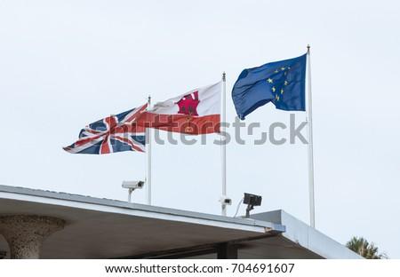 waving flags european union, gibraltar, union jack #704691607