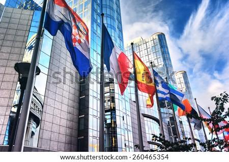 Waving flags in front of European Parliament building. Brussels, Belgium