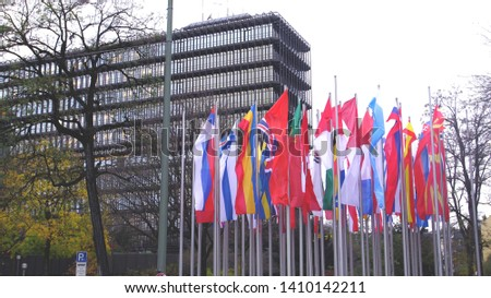 Waving flags next to modern government building #1410142211