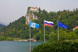 Waving flags of Bled municipality, Slovenia and European Union, with lake and Bled Castle in background.