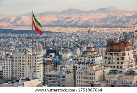 Waving Iran flag above skyline of Tehran at sunset. Stock fotó ©