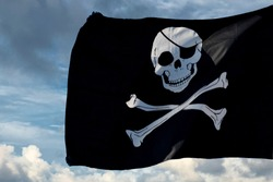 waving pirate flag jolly roger on sky background