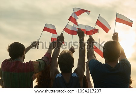 Waving poland flags. Back view silhouette of polish family. #1054217237