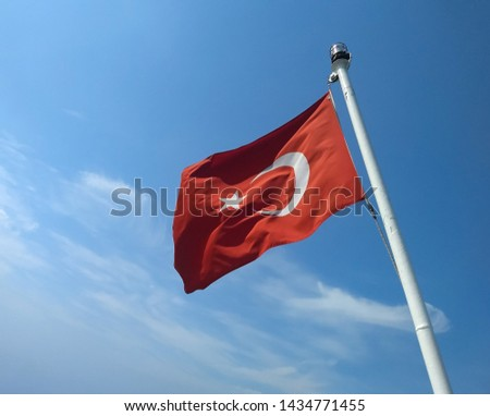 waving turkish flag towards the blue sky on flagpole of boat #1434771455