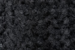 Wavy black faux wool. Artificial wool of a sheep. Fabric texture close-up, useful as a background.