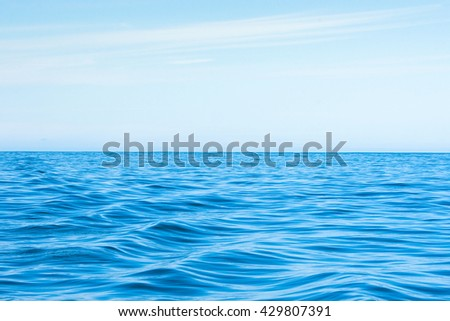 Wavy blue ocean with clouds in the blue sky #429807391